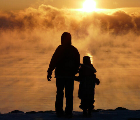 Silhouette of parent and child outside in the sunset