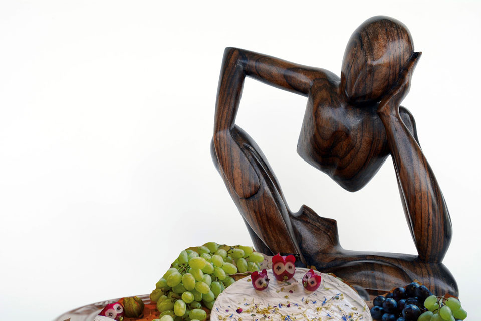 the thinker in wood, eating a buffet