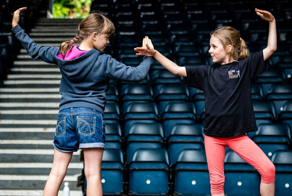 Two young people acting out dramatic confrontation in a Peter Pan workshop in an empty theatre