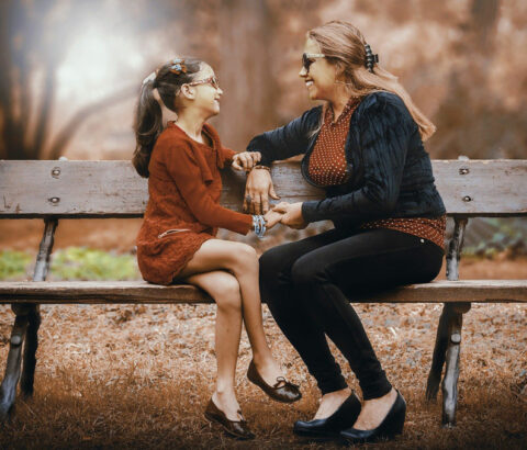 Happy parent and child sitting on a bench in the autumn