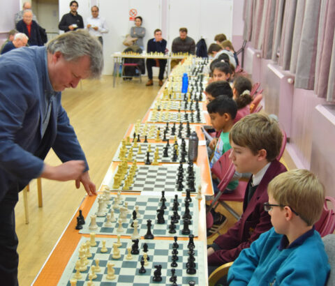 Peter Wells holding a simultaneous chess display