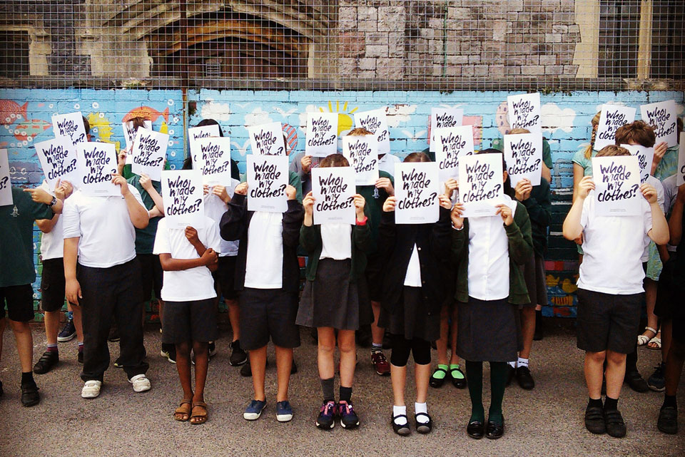A group of school children holding up signs which say Who Made My Clothes