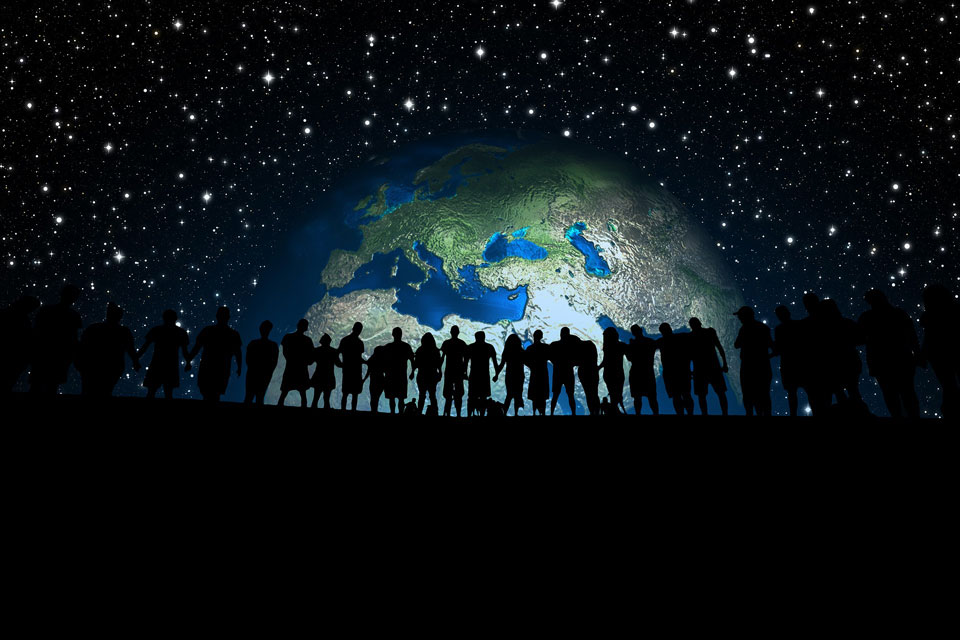 silhouette of humans against a background of the earth in a starfield