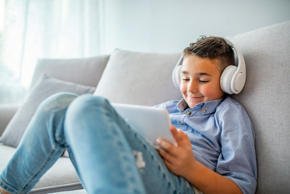 Smiling boy sitting on a sofa listening on headphones and looking at a tablet